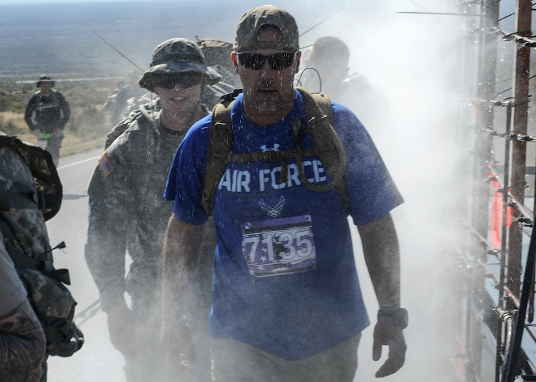 Kenneth Womack, 19th Logistics Readiness Squadron aerial delivery rigger supervisor, passes through a water mist machine along the 26.2 trek of the 2016 Bataan Death March at White Sands Missile Range, N.M., March 20, 2016. The march honors U.S. and Filipino prisoners of war during the notorious Bataan Death March of World War II. Historians estimate the death toll neared 10,000. (U.S. Air Force photo by Senior Airman Harry Brexel)
