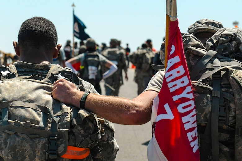 A U.S. Army soldier helps his battle buddy finish the 26.2-mile Bataan Memorial Death March, at White Sands Missile Range, N.M., March 20, 2016. Approximately 6,600 people participated in this year's march, including two teams of Airmen from the 19th Logistics Readiness Squadron. (U.S. Air Force photo by Senior Airman Harry Brexel)