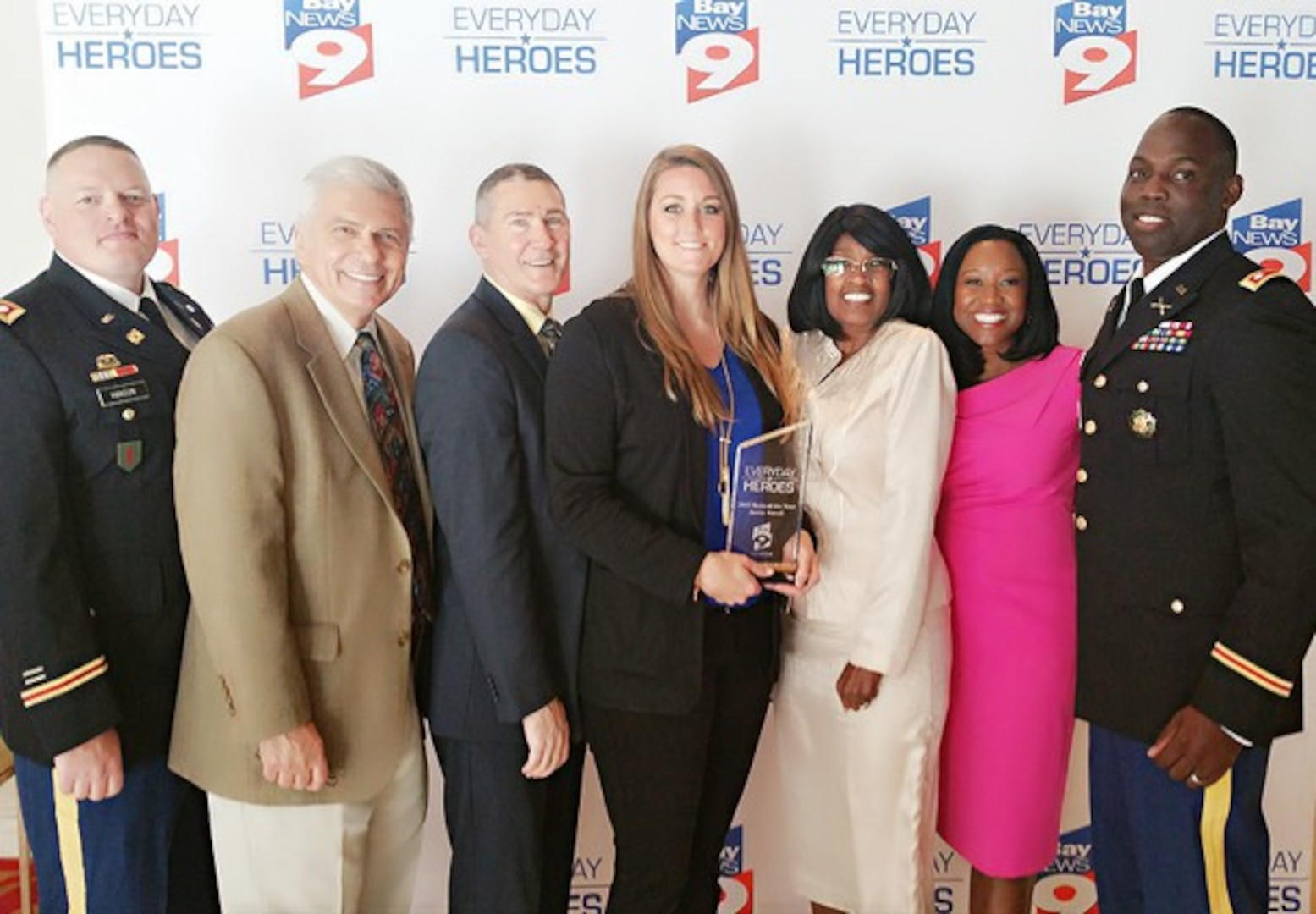 """U.S. Army Reserve 1st Lt. Jessica Purcell (center) receives local area news station Bay News 9's """"2015 Hero of the Year"""" award during a ceremony. Purcell played a key role in the rescue of a 43-year-old Bradenton resident last year. (Photo courtesy of Bay News 9)"""