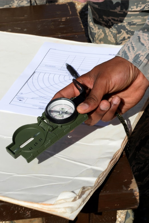 A 736th Security Forces Squadron commando warrior instructor demonstrates how to use a compass during a Prime Base Engineer Emergency Force exercise March 24, 2016, at Andersen Air Force Base, Guam. The Airmen developed their tactical skills to ensure CE personnel can meet impromptu contingency taskings and other unit-specific deployment requirements. (U.S. Air Force Photo/Airman 1st Class Alexa Ann Henderson)
