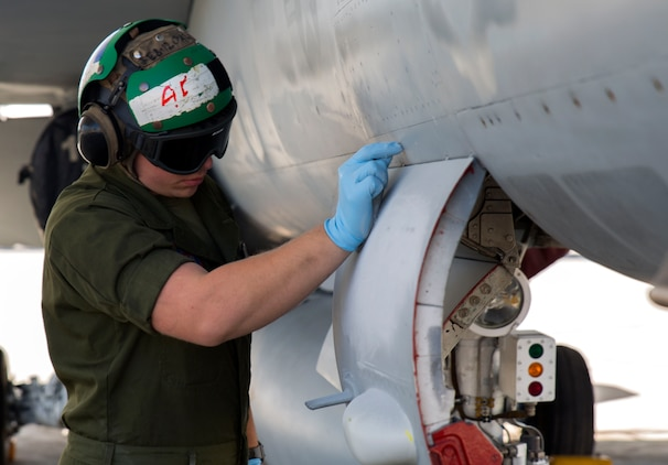 "Lance Cpl. Lestat Lanier, an airframer with Marine Fighter Attack Squadron (VMFA) 122, scrapes letters off an F/A-18C at Marine Corps Air Station Iwakuni, Japan, March 22, 2016. VMFA-122, also known as the ""Werewolves,"" arrived at MCAS Iwakuni March 14 from MCAS Beaufort, S. C., for a six month rotation with the unit deployment program. The Werewolves squadron will conduct contingency, bilateral and multilateral training with their Japanese counterparts and services. (U.S. Marine Corps photo by Cpl. Nicole Zurbrugg/Released)"