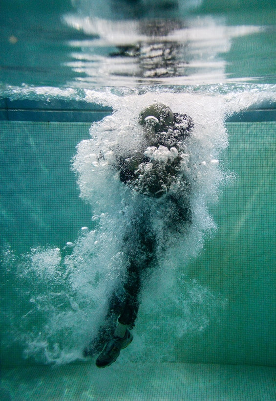 An Airman assigned to Barksdale Air Force Base, La., jumps into a pool during a Survival, Evasion, Resistance and Escape water survival class in Shreveport, La., March 15, 2016. The position reduces the chance of injury from any unseen obstacles underwater. (U.S. Air Force photo/Senior Airman Mozer O. Da Cunha)