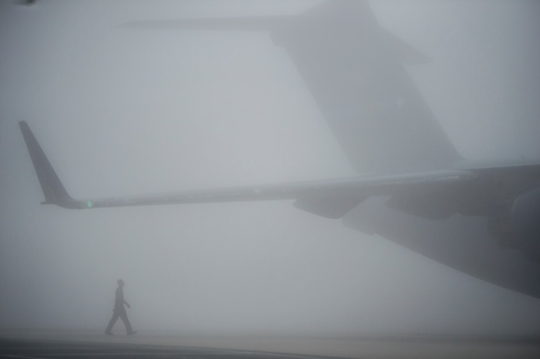 Airman 1st Class Anthony Mahon, of the 436th Airlift Wing, performs a visual inspection on a C-17 Globemaster III during thick fog prior to the aircraft's launch from Dover Air Force Base, Del., March 17, 2016. Experienced reservists from the 512th Airlift Wing frequently train active-duty Airmen in various career field tasks. (U.S. Air Force photo/Capt. Bernie Kale)