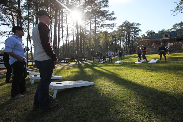 Marines with Marine Attack Training Squadron 203 and their family members play a game of bean bag toss game during the simiannual pig pickin' at Marine Corps Air Station Cherry Point, N.C., March 22, 2016. More than 300 Marines, family members and members of the Havelock community attended the event. The event was held to show the community's appreciation to the Marines and thank the service members on Cherry Point for their contributions to the Marine Air-Ground Task Force. (U.S. Marine Corps photo by Pfc. Nicholas P. Baird/Released)