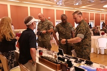 Col. Chandler Seagraves, right, Headquarters and Support Battalion commanding officer, Sgt. Maj. Veney Cochran, middle, Headquarters and Support Battalion sergeant major and Lt. Col. Giles Walger, Headquarters and Support Battalion executive officer look at sample memorabilia available at the Marine Corps Ball Expo at Marston Pavilion on Marine Corps Base Camp Lejeune March 15. Marine Corps Community Services hosted the expo to aid Marines plan their balls by linking vendors with members of unit ball committees.