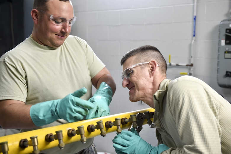 Tech. Sgt. Frank Serrao and Tech. Sgt. Thomas Neiswanger, aerial spray maintenance craftsmen with the 910th Maintenance Squadron, remove nozzles from an aerial spray boom for inspection and cleaning here, March 24. Aerial spray maintainers come from traditional aircraft maintenance jobs, learning a unique skillset through on-job training to maintain the equipment for the Department of Defense's only aerial spray mission. The aerial spray mission includes insect control, vegetation control on bombing ranges and oil spill neutralization.  (U.S. Air Force photo/Eric M. White)