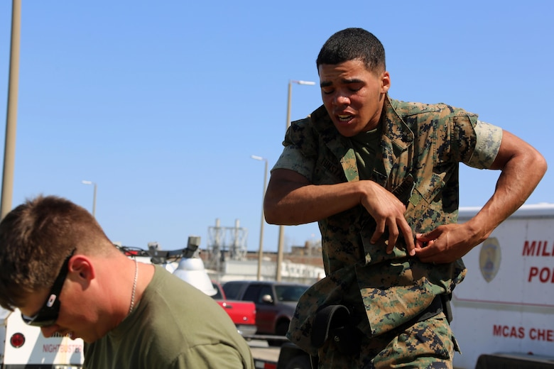 Lance Cpl. Xavier Tunstall simulates handcuffing personnel during non-lethal weapons training at Marine Corps Air Station Cherry Point, N.C., March 17, 2016. Twelve Marines from various units participated in the training event with the Provost Marshal's Office. Marines were sprayed in the face with the potent substance and then maneuvered through an obstacle course simulating non-compliant threats. The training familiarized the participants with both the gear they will carry and the effects it will have on an individual being sprayed. Tunstall is an administrative clerk with Headquarters and Headquarters Squadron. (U.S. Marine Corps photo by Cpl. N.W. Huertas/Released)