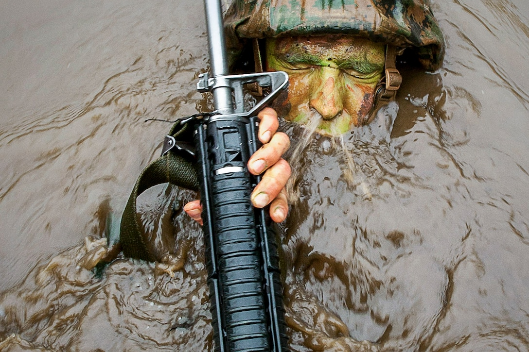 A Marine Corps officer candidate breaks the surface of the Quigley, a murky water obstacle used for training, at the Officer Candidates School on Marine Corps Base Quantico, Va., March 15, 2016. The candidate is assigned to Delta Company, Officer Candidates Class 221. Marine Corps photo by Cpl. Patrick H. Owens