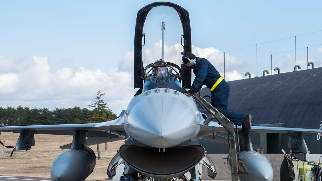 U.S. Air Force Airman Joseph Farmer, a crew chief with the 35th Maintenance Squadron, helps secure Lt. Col. Paul Miller, the deputy commander of the 35th Operations Group, into an F-16 Fighting Falcon during exercise Beverly Sunrise 16-03 at Misawa Air Base, Japan, March 23, 2016. Before and after flight, crew chiefs perform inspections, ensuring a safe flight for the pilot. (U.S. Air Force photo by Airman 1st Class Jordyn Fetter)