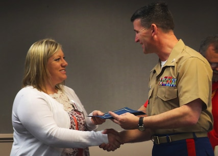 Jenna Kauffman receives her District Spouse Orientation Course completion certificate from Col. Jeffrey Smitherman March 25, 2016, at the Marine Bachelor's Quarters on Beaufort Air Station. The DSOC program is to help spouses establish and connect a support network with other recruiting spouses. In addition, they receive classes on how to strengthen their marriages with their Marines. Kauffman is a spouse from Recruiting Station Nashville, 6th Marine Corps District. Smitherman is the commanding officer of the 6th Marine Corps Recruiting District, Parris Island, South Carolina. (Official Marine Corps photo by Cpl. Diamond N. Peden/Released)