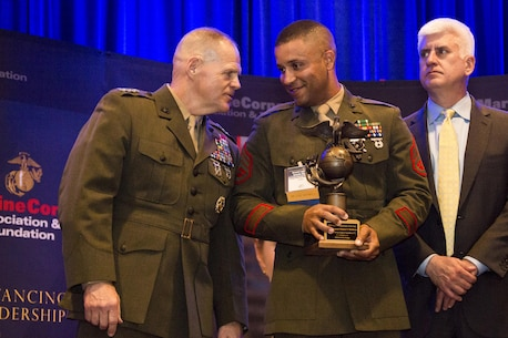 U.S. Marine Corps Staff Sgt. Deacon T. Matthews, center, listens to Commandant of the Marine Corps Gen. Robert B. Neller, left, during the 12th Marine Corps Association and Foundation Ground Logistics Awards dinner at the Crystal Gateway Marriot, Arlington, Va., March 24, 2016. Matthews was awarded the 2015 Marine Corps enlisted logistician of the year. (U.S. Marine Corps photo by Staff Sgt. Gabriela Garcia/Released)