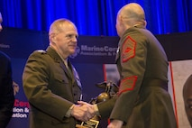 Commandant of the Marine Corps Gen. Robert B. Neller congratulates a Marine during the 12th Marine Corps Association and Foundation Ground Logistics Awards dinner at the Crystal Gateway Marriot, Arlington, Va., March 24, 2016. The annual event recognized the professional achievements of the top performing Marine logisticians and logistics unit of the year for the previous year. (U.S. Marine Corps photo by Staff Sgt. Gabriela Garcia/Released)
