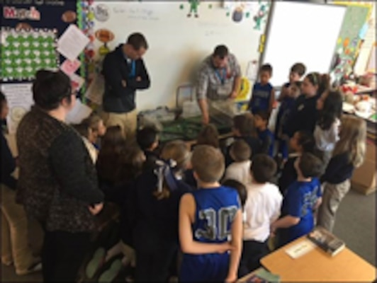 Bryce Carmichael and Kent Smith met St. Joseph Catholic School students to discuss engineering and show them how USACE uses various structures to reduce flooding impacts. The students observing the flood plain management model.