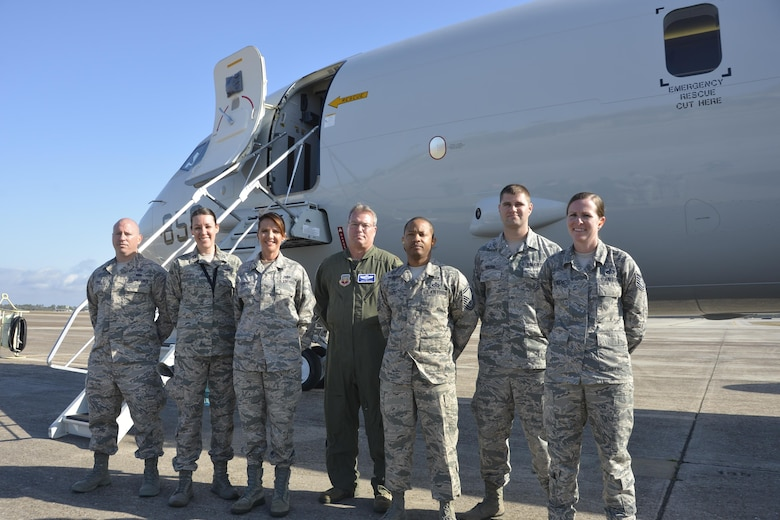A cross section of military specialties to include operations, intelligence and communications, came together here March 14 for an incentive flight aboard a Navy P-8A Poseidon from Naval Air Station Jacksonville, Fla. March 14. The aircraft was here to present a working demonstration to Air Forces Northern leadership about the viability of using imagery-feed capabilities from the P-8A Poseidon during a Defense Support of Civil Authorities  event. From left: Master Sgt. Kevin Hale, intelligence; Capt. Renee Popoff, intelligence; Tech. Sgt. Tamara Murphy, communications; Maj. Jeffrey Rayhill, operations; Senior Master Sgt. Robert Gentry III, operations; Senior Airman Phillip Holzer, intelligence; and Tech. Sgt. Bridget Behrens, operations. While aboard, the Airmen, who each had a partial role in the larger demonstration effort, got to watch onboard operations during the flight. (Air Force  Photo Released/Mary McHale)