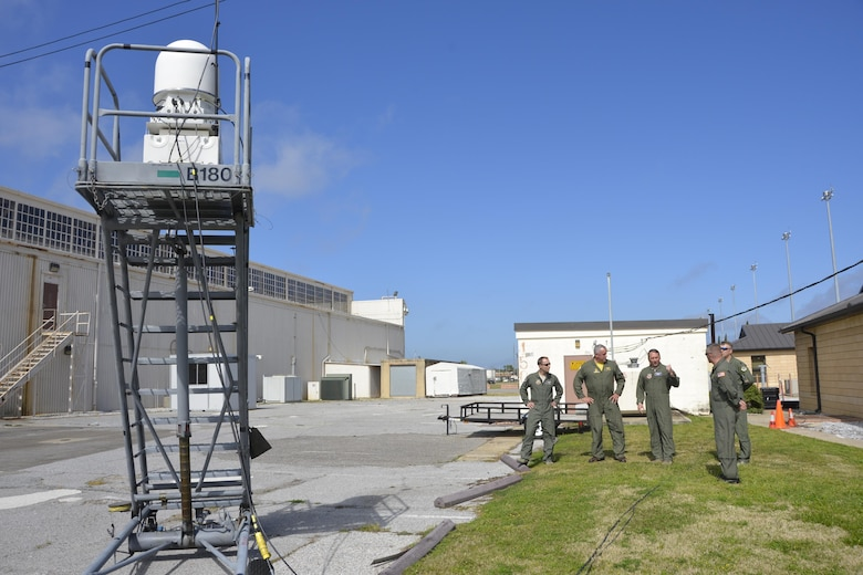 (Center) Brig. Gen. David Hicks, Air Forces Northern Vice Commander, discusses the radar that's part of the ground-based equipment suite during the P-8A Poseidon imagery-generation demonstration at Tyndall Base Operations March 14. The aircraft was here to present a working demonstration to Air Forces Northern leadership about the viability of using imagery feed from the platform during a Defense Support of Civil Authorities  event. During the demonstration, the P-8A Poseidon-generated imagery to the ground-based station as it flew in Northwest Florida airspace. Seven Airmen from Air Forces Northern flew aboard the aircraft during the demonstration to watch onboard operations during the flight. (Air Force  Photo Released/Mary McHale)