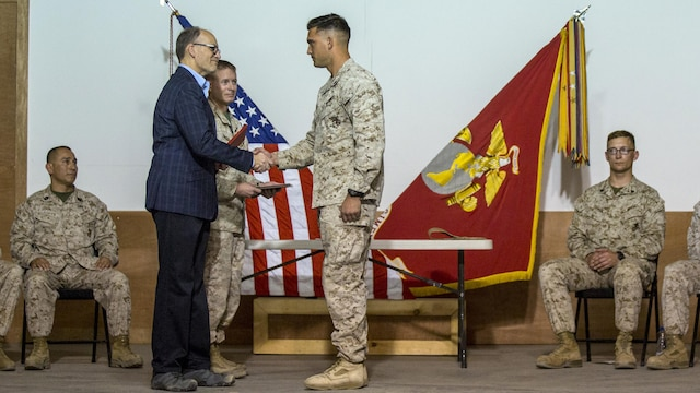Ambassador Douglas A. Silliman, second from left, the U.S. Ambassador to Kuwait, along with U.S. Marine Col. William F. McCollough, commanding officer of Special Purpose Marine Air Ground Task Force-Crisis Response-Central Command, present the Corporals Course graduates with their diplomas in Kuwait on March 25, 2016. The corporals' leadership program is designed to provide instruction for tasks developed in accordance with Marine Corps Order 1510.90, Individual Training Standards. Corporals Course is a professional military education requirement for all corporals to complete in order to be qualified for promotion.