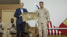 U.S. Marine Cpl. Andrew Gabriel, right, a scout sniper with Charlie Company, 1st Battalion, 7th Marine Regiment, Special Purpose Marine Air Ground Task Force-Crisis Response-Central Command, presents Ambassador Douglas A. Silliman, the U.S. Ambassador to Kuwait, with a gift during the Corporals Course graduation ceremony in Kuwait on March 25, 2016. The corporals' leadership program is designed to provide instruction for tasks developed in accordance with Marine Corps Order 1510.90, Individual Training Standards. Corporals Course is a professional military education requirement for all corporals to complete in order to be qualified for promotion.