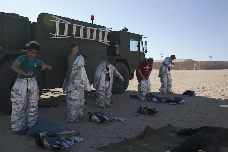 Boy scouts with Troop 180 race to put on fire retardant suits under the supervision of Marines from Marine Wing Support Squadron 374 during a Boy Scout Camp Out at Camp Wilson, March 19, 2016. (Official Marine Corps photo by Cpl. Medina Ayala-Lo/Released)
