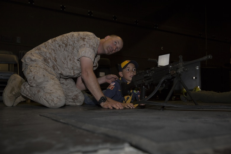 Maj. Jamison Fox, officer in charge, Exercise Logistics Coordination Center, instructs his son, Aiden, 8, cub scout, troop 78, on the operation of the M249 Squad Automatic Weapon at the Indoor Simulated Marksmanship Trainer during the Boy Scout Camp Out for local Boy Scouts of America troops March 18, 2016. (Official Marine Corps photo by Sgt. Charles Santamaria/Released)