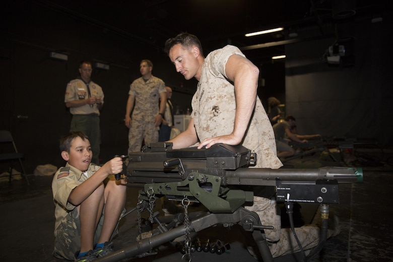 Cpl. Matthew Barnes, assaultman, 3rd Battalion, 7th Marine Regiment, observes the Mark 19 Grenade Launcher as Devin Castanon, 12, boy scout, Troop 72, prepares to fire at the Indoor Simulated Marksmanship Trainer during the Boy Scout Camp Out for local Boy Scouts of America troops March 18, 2016. (Official Marine Corps photo by Sgt. Charles Santamaria/Released)