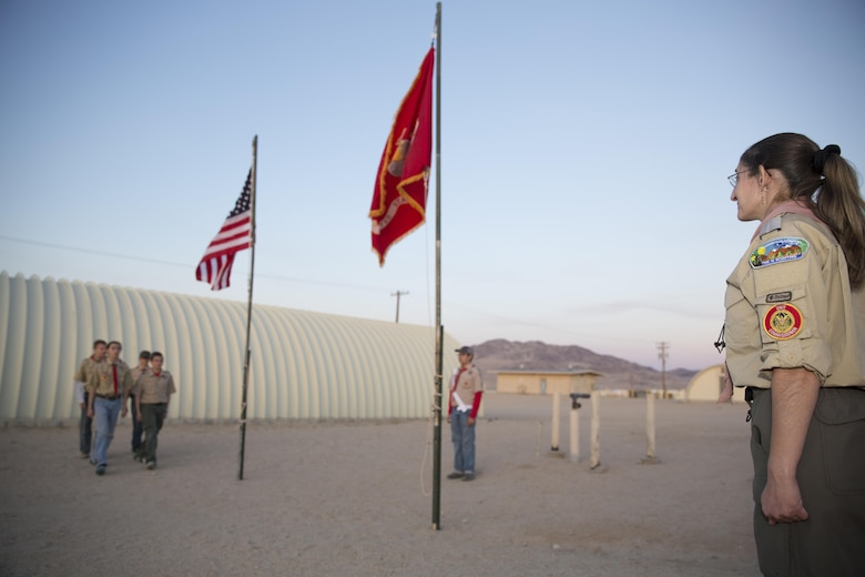 Nicole Fenstermaker, unit commissioner, Boy Scouts of America stands at the position of attention as Troop 77's color guard detail prepare to retrieve the National and Marine Corps colors at Camp Wilson before the evening colors ceremony as part of the Boy Scout Camp Out for local Boy Scouts of America troops March 18, 2016. (Official Marine Corps photo by Sgt. Charles Santamaria/Released)