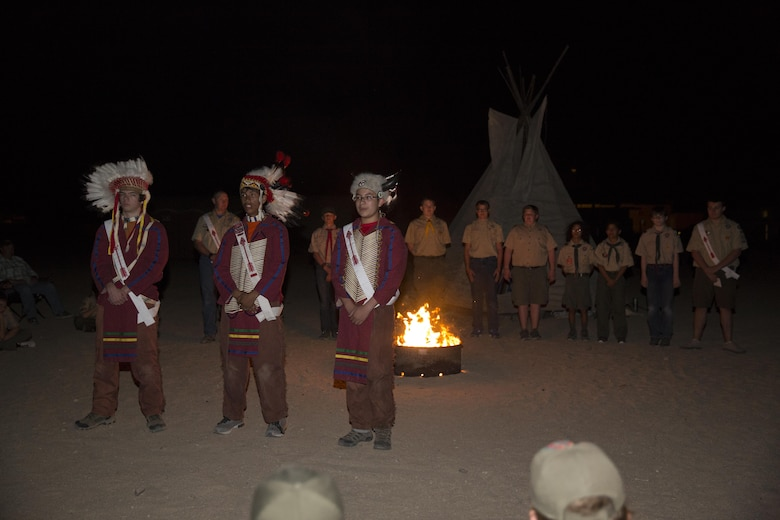 Order of the Arrow nominees stand on line as three members of the order, dressed in Native American regalia to honor the past, give background on what the nomination of the scouts behind them signifies during their Call Out Ceremony at Camp Wilson as part of the Boy Scout Camp Out for local Boy Scouts of America troops March 18, 2016. The annual ceremony selects scouts who were nominated by their peers for exemplary scouting skills, leadership and willingness to learn. The order is an honor society within the organization symbolized by a white sash with a red arrow for members who have been officially accepted. (Official Marine Corps photo by Sgt. Charles Santamaria/Released)