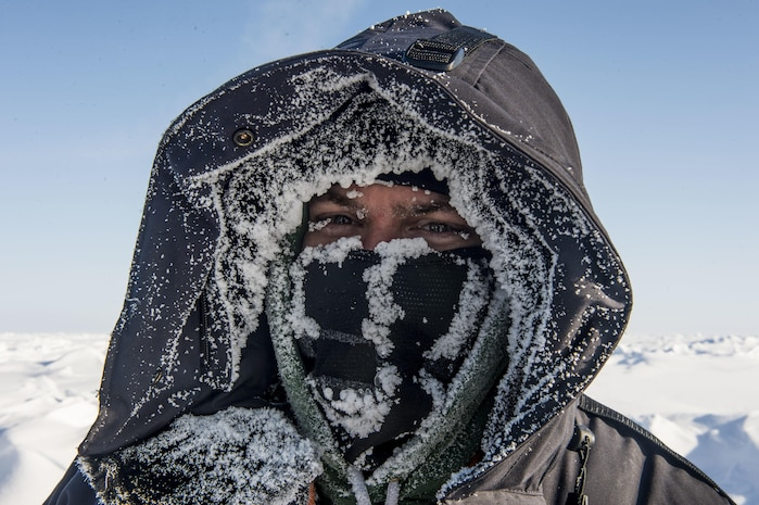 A man's face is almost obscured by winter clothing and a snow-dusted mask.