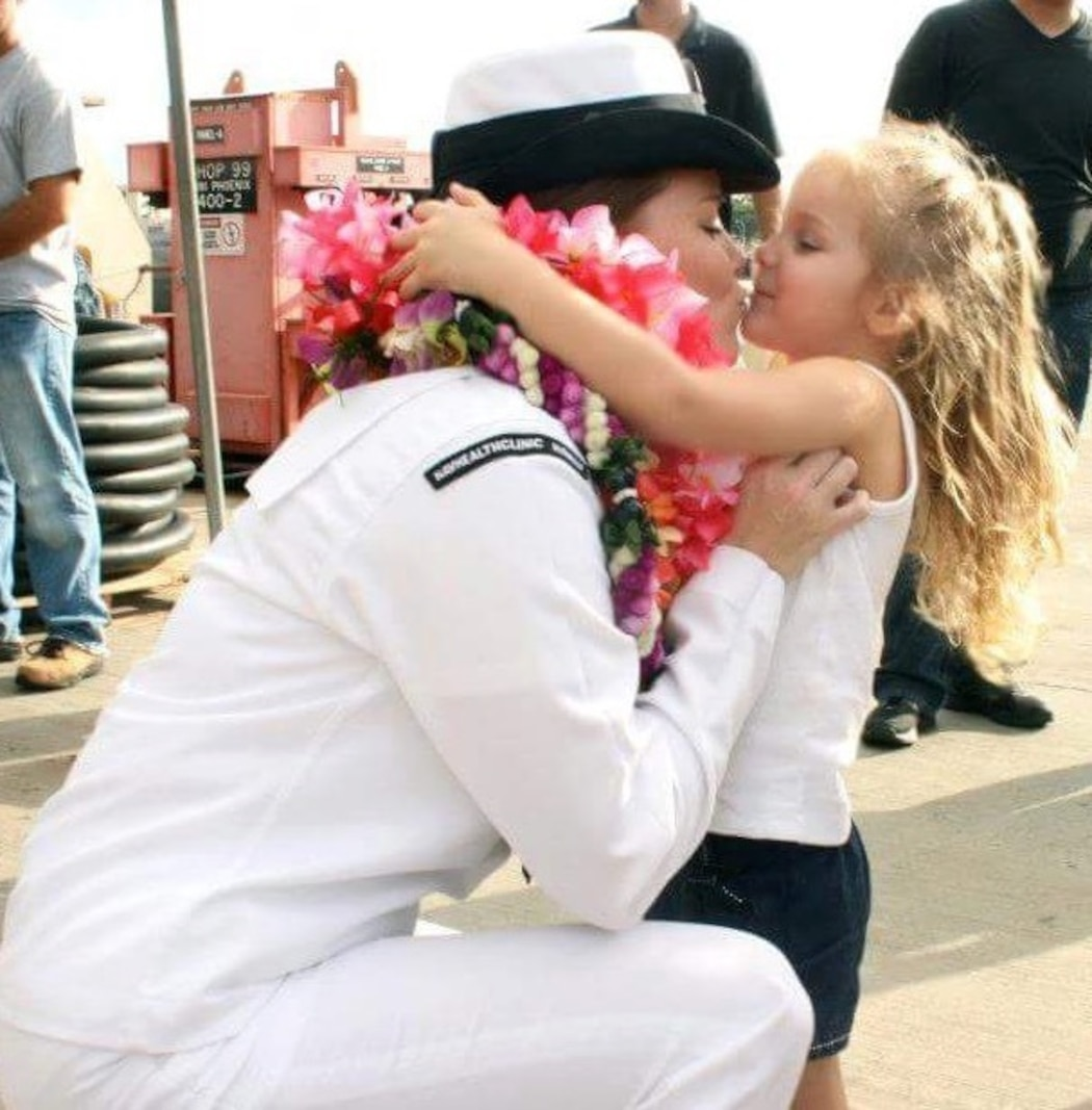 Chief Petty Officer Jaclyn Place kisses her daughter. Place is a lead chief petty officer with the Headquarters Regimental Aid Station, 1st Marine Logistics Group, and was awarded an impact Navy and Marine Corps Commendation Medal for her selfless and decisive actions that saved the lives of her neighbors. (U.S. Marine Corps photo by Sgt. Laura Gauna/released)