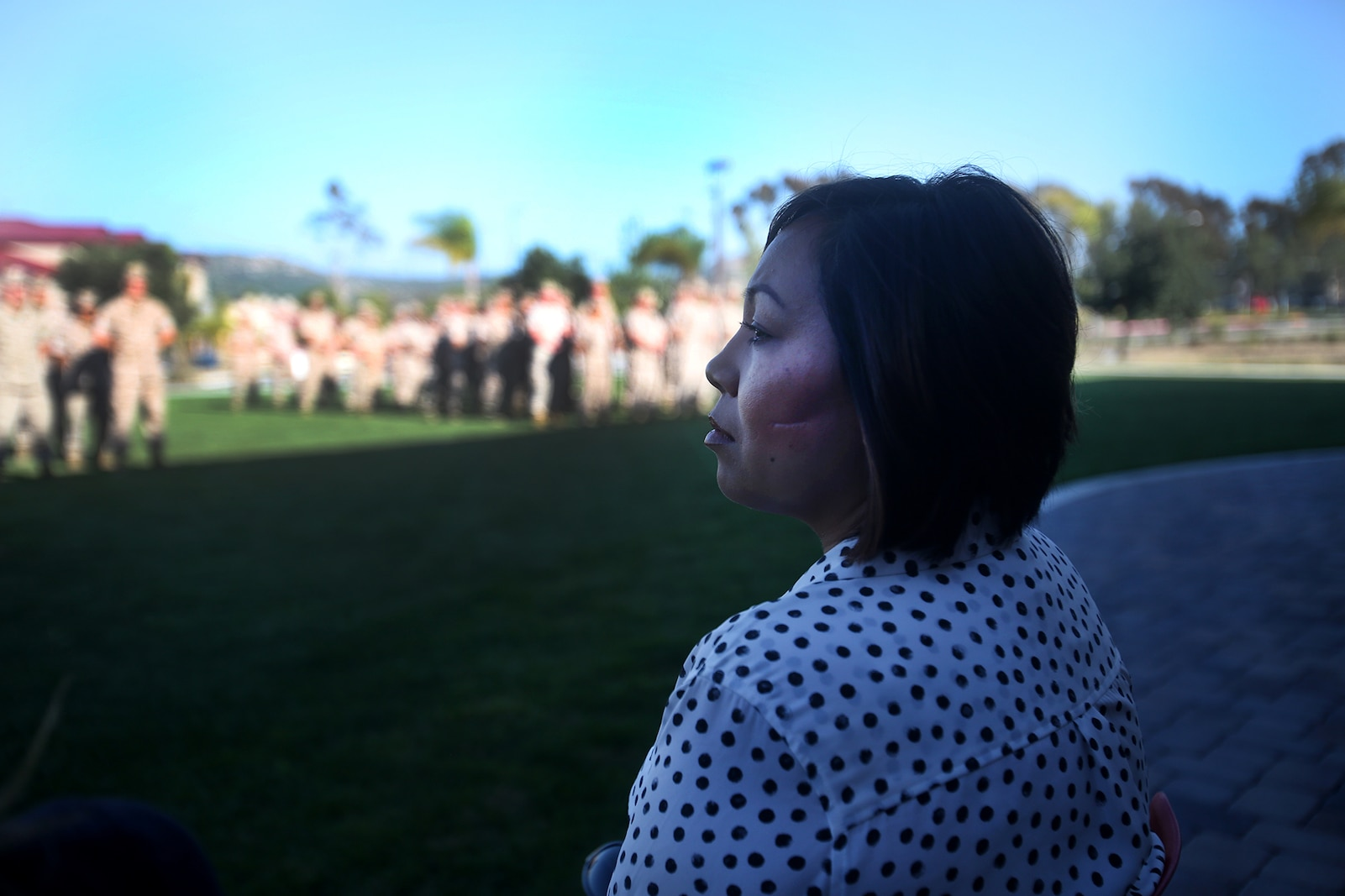 Jennifer Barela, one of Chief Petty Officer Jaclyn Place's neighbors and the survivors of the brutal attack, looks out at dozens of Marines during Place's award ceremony aboard Camp Pendleton, Calif., March 11, 2016. Place, a lead chief petty officer with the Headquarters Regimental Aid Station, 1st Marine Logistics Group, was awarded an impact Navy and Marine Corps Commendation Medal for her selfless and decisive actions that saved the lives of Barela and her daughter. (U.S. Marine Corps photo by Sgt. Laura Gauna/released)