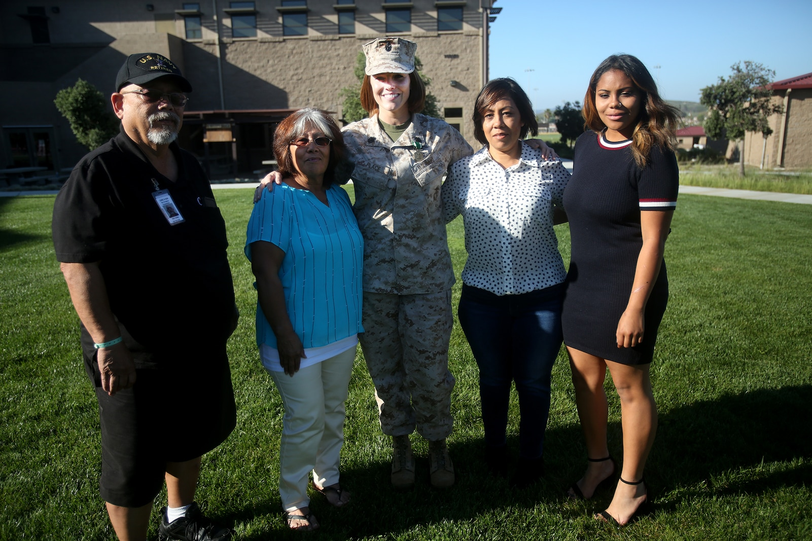 Chief Petty Officer Jaclyn Place poses for a photo with her neighbors and their family during Place's award ceremony aboard Camp Pendleton, Calif., March 11, 2016. Place is a lead chief petty officer with the Headquarters Regimental Aid Station, 1st Marine Logistics Group, and was awarded an impact Navy and Marine Corps Commendation Medal for her selfless and decisive actions that saved the lives of her neighbors. (U.S. Marine Corps photo by Sgt. Laura Gauna/released)