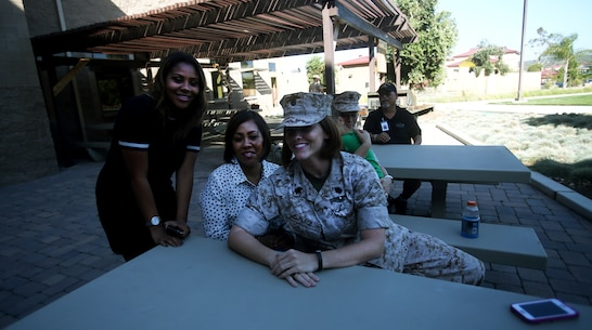 Chief Petty Officer Jaclyn Place poses for a photo with her neighbors during Place's award ceremony aboard Camp Pendleton, Calif., March 11, 2016. Place is a lead chief petty officer with the Headquarters Regimental Aid Station, 1st Marine Logistics Group, and was awarded an impact Navy and Marine Corps Commendation Medal for her selfless and decisive actions that saved the lives of her neighbors. (U.S. Marine Corps photo by Sgt. Laura Gauna/released)