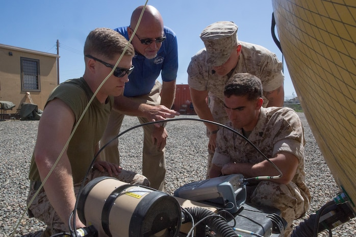 """Matt Macon, a satellite communications operator contractor, shows field radio operators with the 11th Marine Expeditionary Unit how to use a satellite communications dish during a communications exercise (COMMEX) aboard Marine Corps Base Camp Pendleton, Calif., March 23, 2016. The COMMEX familiarizes Marines with the 11th MEU's standing operating procedures regarding communications as they prepare to begin training or """"work-ups"""" leading to the upcoming deployment."""