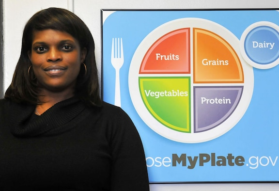 Sonja L. Cooke, JBAB dietitian, poses with the MyPlate Diagram, a guide to help people make well balanced meals. She says managing the quality, frequency and portion control of your meals can help people on their way to living a healthier lifestyle. (U.S. Navy Photo by Christopher Hurd, Joint Base Journal)