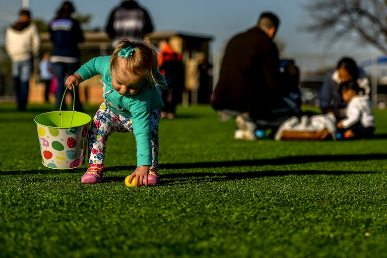 A one-year-old girl picks up an Easter egg at the softball field on Goodfellow Air Force Base, Texas, March 26, 2016. The 17th Force Support Squadron hosted the Easter egg hunt to celebrate the holiday with Goodfellow families. (U.S. Air Force photo by Senior Airman Devin Boyer/Released)