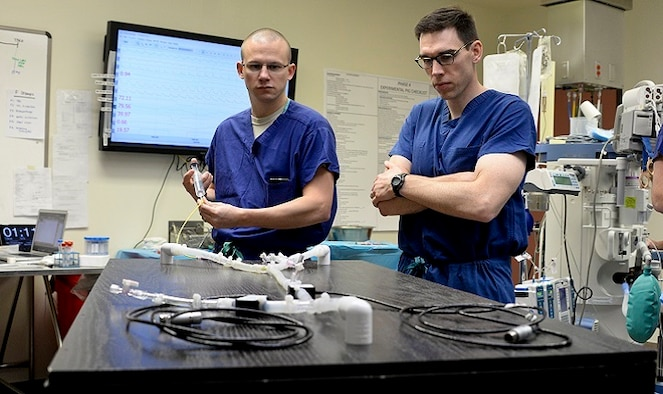 Air Force Majors Timothy Williams, left, and Lucas Neff, right, perform bench top testing of balloon catheters at Travis Air Force Base, Calif., using a custom-made blood flow simulator. The Clinical Investigation Facility, located at David Grant USAF Medical Center, is the research facility where the REBOA catheter came to fruition. (U.S. Air Force photo by Senior Airman Amber Carter)