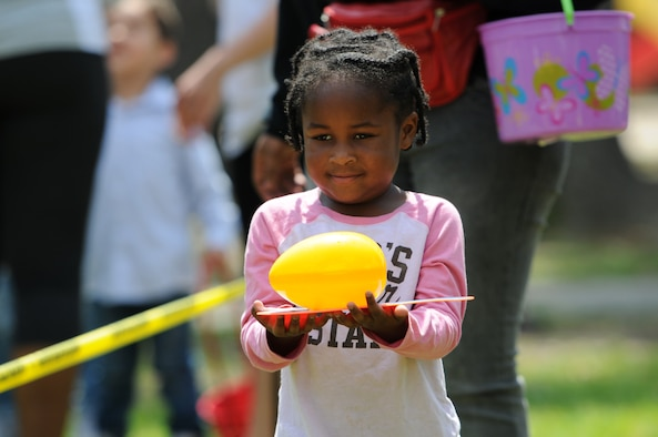 Lovely Arnold, daughter of Staff Sgt. Duron Arnold, 81st Security Forces Squadron unit deployment manager, participates in a balancing egg game during Easter in the Park at the marina Mar. 26, 2016, Keesler Air Force Base, Miss. The event also included an egg hunt, a youth fun run, arts and crafts and visits with the Easter Bunny. (U.S. Air Force photo by Kemberly Groue)