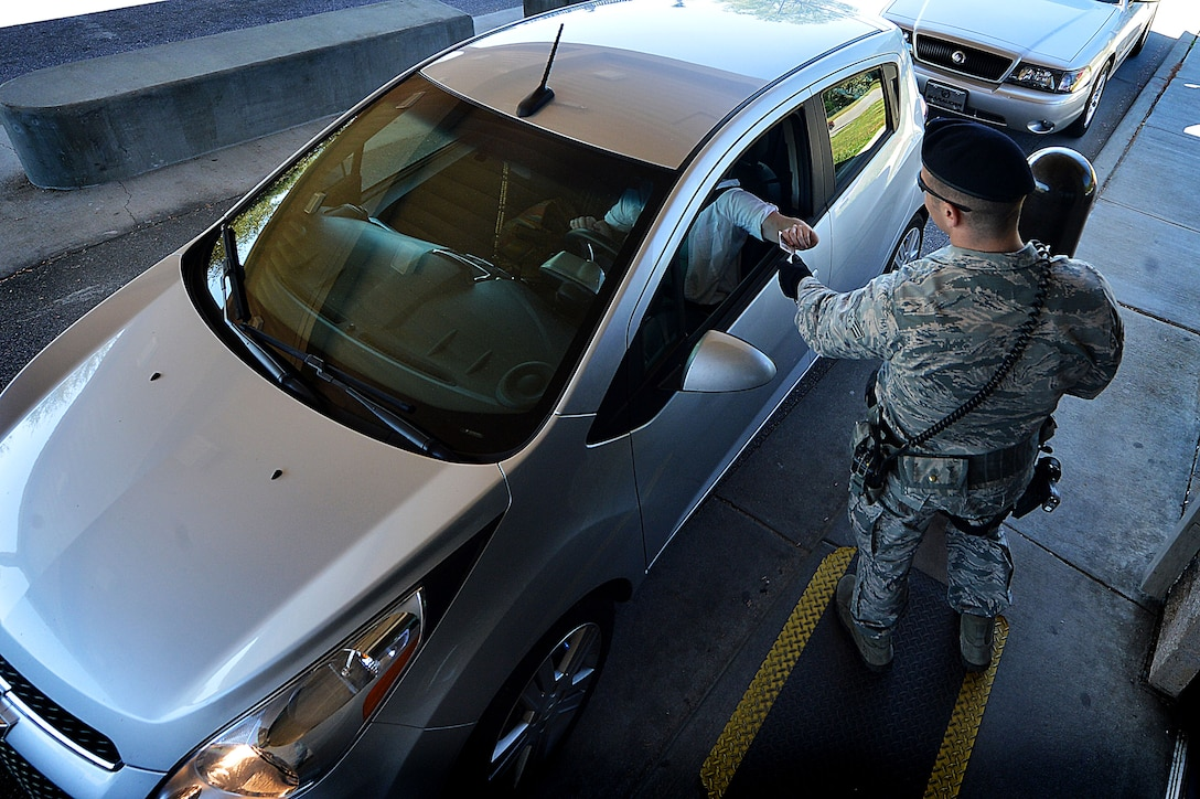 U.S. Air Force Senior Airman Samuel Montgomery, 20th Security Forces Squadron patrolman, inspects identification cards at the Main Gate at Shaw Air Force Base, S.C., March 29, 2016. 20th SFS Airmen are tasked with ensuring the security of the base and its assets while simultaneously protecting members of Team Shaw and their families. (U.S. Air Force photo by Senior Airman Michael Cossaboom)