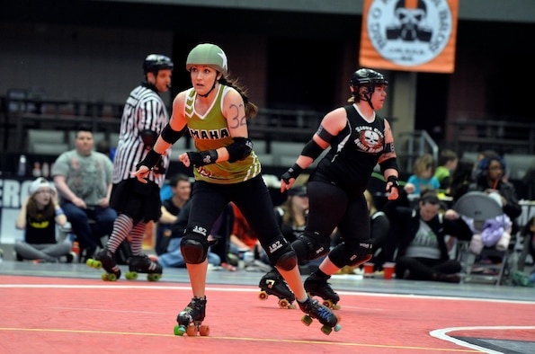 U.S. Air Force Maj. Jocelyn Smith, an executive officer with the 55th Wing Headquarters, skates past a blockade of Sioux City Roller Dames at the Ralston Arena, Neb., March 26, 2016. Smith, one a member of the Omaha Rollergirls, has been a participating in the roller derby sport for XX years.  (U.S. Air Force photo by Josh Plueger/Released)