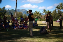 MARINE CORPS TRAINING AREA BELLOWS – Marines and civilian officers from the Provost Marshal's Office Military Working Dogs Unit with Headquarters Battalion from Marine Corps Base Hawaii answer questions and explain the importance of their job to a Cub Scout Troop aboard Marine Corps Training Area Bellows, March 5, 2016. Marines and civilian officers gave different commands to their dogs, showing off their intelligence and obedience. The dog handlers also wore a bite jacket for a mock take down by the dogs to show the scouts the discipline and training the dogs show when facing a real threat. (U.S. Marine Corps Photo by Lance Cpl. Jesus Sepulveda Torres)