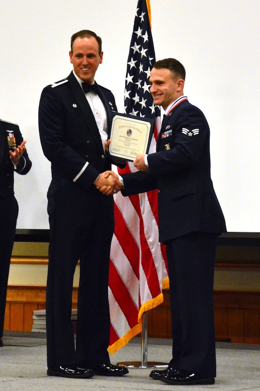 120th Airlift Wing Commander Col. Lee Smith presents an Airman Leadership School diploma to Senior Airman Nicholaus Schwall, March 22, 2016. Schwall was one of 32 students who graduated from ALS Class 16-D at Malmstrom Air Force Base, Mont. (U.S. Air National Guard photo by Senior Master Sgt. Eric Peterson)