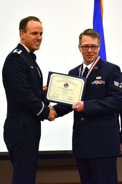 120th Airlift Wing Commander Col. Lee Smith presents an Airman Leadership School diploma to Senior Airman Nikolas Asmussen, March 22, 2016. Asmussen was one of 32 students who graduated from ALS class 16-D at Malmstrom Air Force Base, Mont. (U.S. Air National Guard photo by Senior Master Sgt. Eric Peterson)