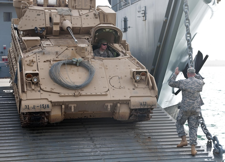 Kuwait Naval Base, Kuwait –A Bradley Fighting Vehicle rolls off the ramp of an Army Logistics Support Vessel during a training exercise.  Army watercraft are designed to operate in austere to bare beach environment and are not dependent upon developed seaports or infrastructure.  1TSC has a vested interest in the operational ability of Army vessels as they are integral to meeting heavy sustainment lift requirements. (US Army photo by Master Sgt. Dave Thompson, 1TSC Public Affairs)