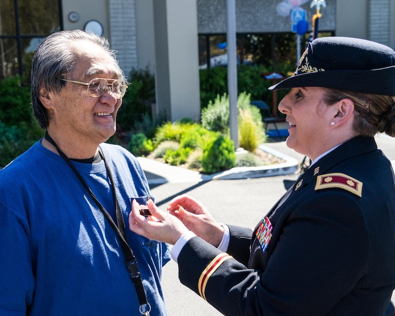 """Maj. (Retired) Andrea Singer, the 311th Sustainment Command (Expeditionary) Resource Management Officer, presents Vietnam Veteran Lapel Pins to vets at the West Los Angeles Vet Center, Culver City, Calif., March 29, 2016. Engraved on the pins is """"A Grateful Nation Thanks and Honors You."""""""