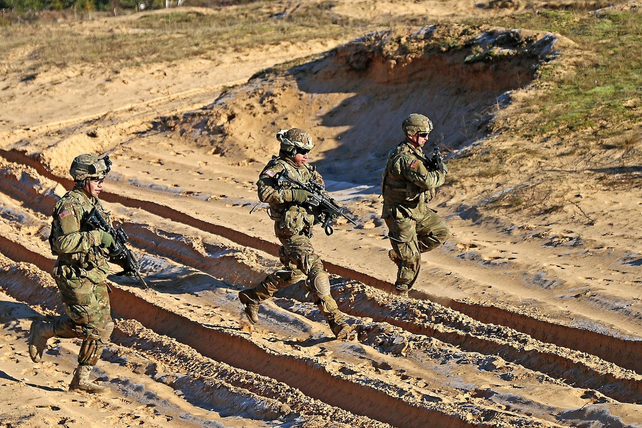Army Spc. Devon Rivera, left, Army Sgt. Jorge Martinez and Army Pfc. Justin Giaimo, right, all indirect-fire infantrymen assigned to Headquarters and Headquarters Troop, 3rd Squadron, 2nd Cavalry Regiment, bound to a fighting position while rehearsing before a multinational mortar live fire exercise alongside Latvian partners at Adazi Military Base, Latvia, Feb. 17, 2016. As part of the U.S. commitment to increased assurance and deterrence, U.S. Army Europe will begin receiving continuous troop rotations of U.S.-based armored brigade combat teams to the European theater in early 2017, bringing the total Army presence in Europe up to three fully-manned Army brigades. U.S. Army photo by Sgt. Paige Behringer