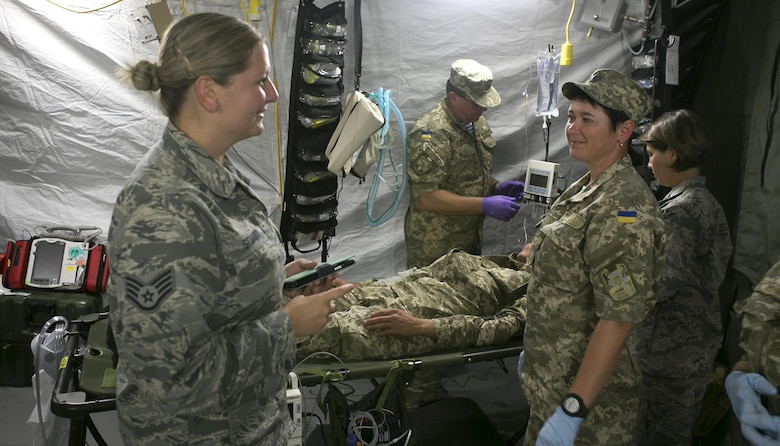 Staff Sgt. Anastasia Stuart, left, assigned to the 6th Medical Support Squadron, translates instructions about the medical equipment in Zhytomyr, Ukraine, Aug. 18, 2015. Stuart was selected by the Language Enabled Airman Program to interpret and translate between U.S Air Force Airmen and Ukrainian soldiers. (Courtesy photo)