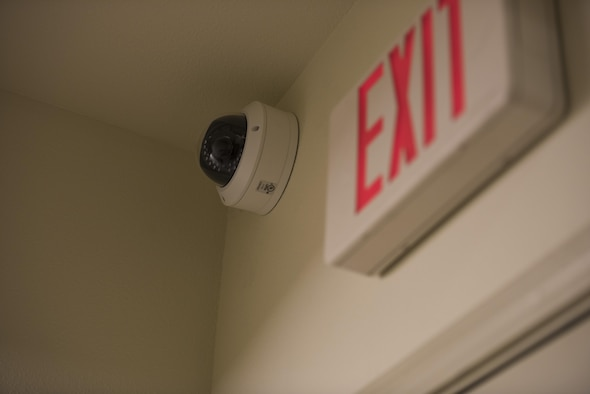 A security camera is positioned above one of the dorm building 2412 exits at Mountain Home Air Force Base, Idaho, March 23, 2016.The cameras are planned to be installed in public areas of every dorm building on base in order to improve the security and quality of life for dorm residents. (U.S. Air Force photo by Airman Alaysia Berry/RELEASED)