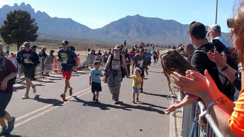 U.S. Air Force Tech. Sgt. Julia Getter, 53rd Test Support Squadron, crosses the finish line with her sons, 7-year-old Zackary and 2-year-old Zander, at the Bataan Memorial Death March, White Sands Missile Range, New Mexico, March 20, 2016. This was Getter's fifth time participating in the Bataan Memorial Death March, which is held in honor of the service members who defended the Philippine Islands during World War II and were captured by the Japanese in 1942. (Courtesy photo/Released)
