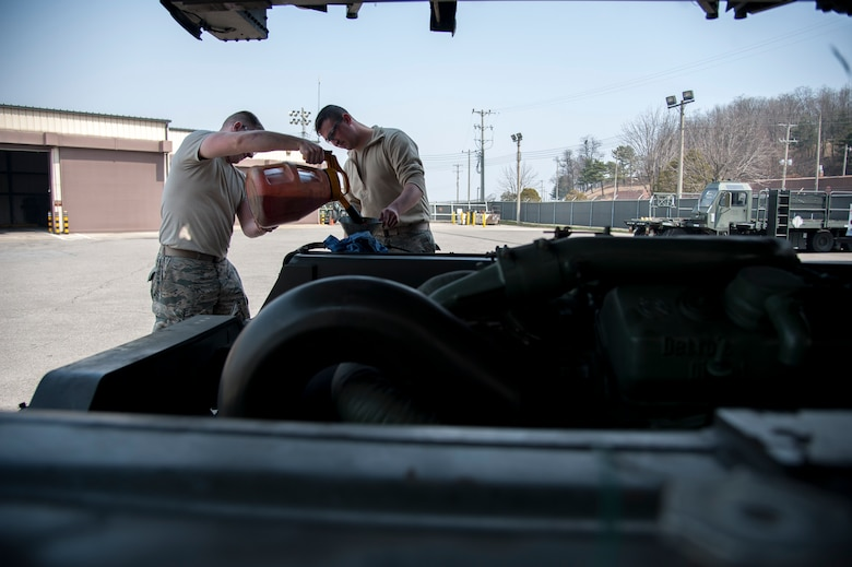 Senior Airman Zachery White and Senior Airman Jonathan Rowley, 51st Logistics Readiness Squadron sorting generating and aircraft sustaining vehicle maintainers, work together to fill a hydraulic fluid reservoir at Osan Air Base, Republic of Korea on March 30, 2016. White and Rowley inspected a Tunner 60K loader to ensure operational order. (U.S. Air Force photo by Staff Sgt. Jonathan Steffen/Released)