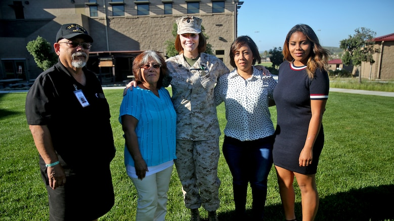 Chief Petty Officer Jaclyn Place poses for a photo with her neighbors and their family during Place's award ceremony at Marine Corps Base Camp Pendleton, California, March 11, 2016. Place is a lead chief petty officer with the Headquarters Regimental Aid Station, 1st Marine Logistics Group, and was awarded an impact Navy and Marine Corps Commendation Medal for her selfless and decisive actions that saved the lives of her neighbors.
