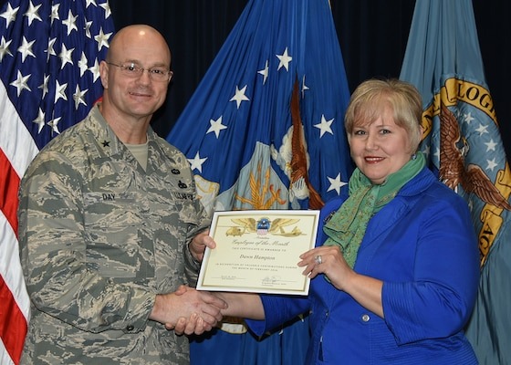 Defense Logistics Agency Aviation Commander Air Force Brig. Gen. Allan Day presents the February Employee of the Month Award to Dawn Hampton during a ceremony March 28, 2016, at Defense Supply Center Richmond, Virginia. Hampton is a price analyst for DLA Aviation's Procurement Process Support Directorate's Pricing Division.